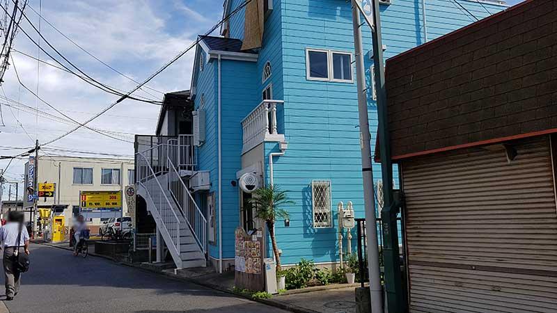 水色のかわいい建物と渦マークの看板が目印