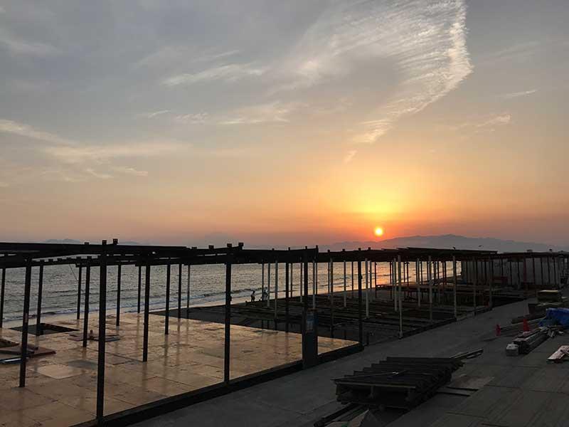 沈む夕日とスケルトンの海の家