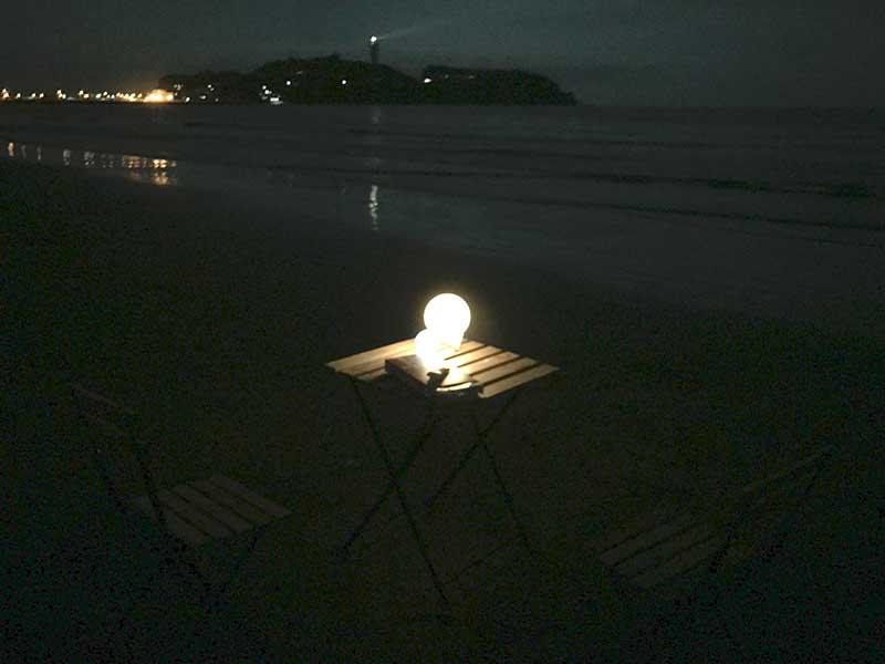 浜辺にテーブルと椅子が置いてあるだけ