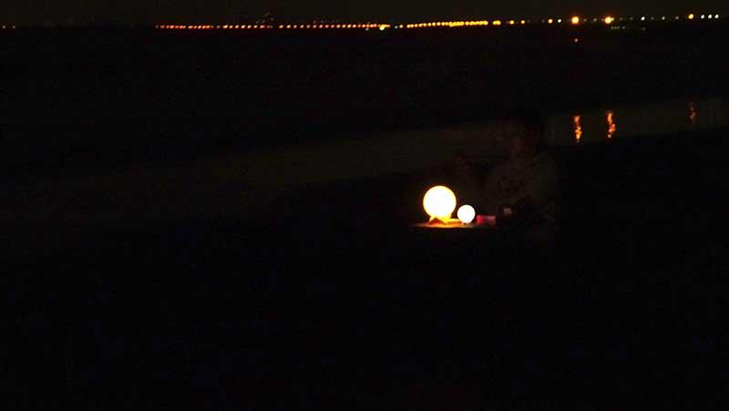 夜の砂浜にじんわり灯りが