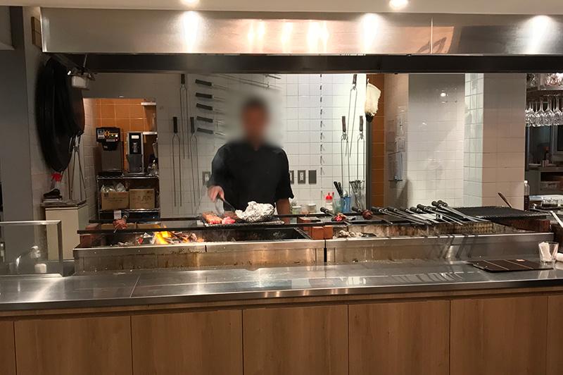 オープンキッチンのグリルでジュージュー焼かれるシュラスコ