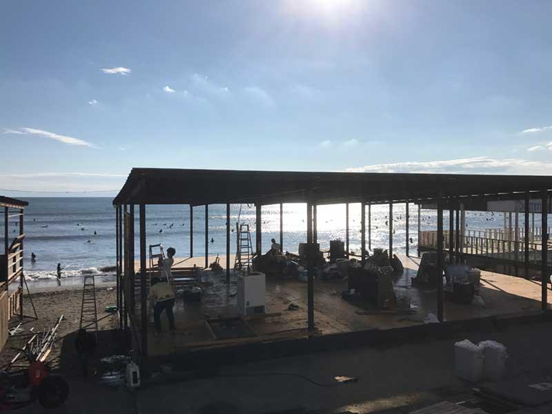 解体中の海の家の合間から見えるサーファーの姿