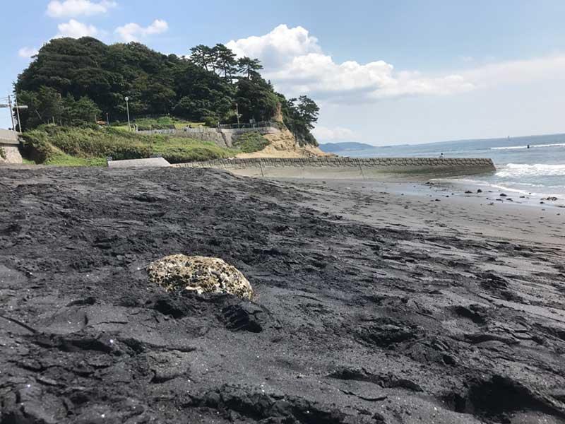 黒い砂鉄混じりの稲村ヶ崎海岸の砂浜