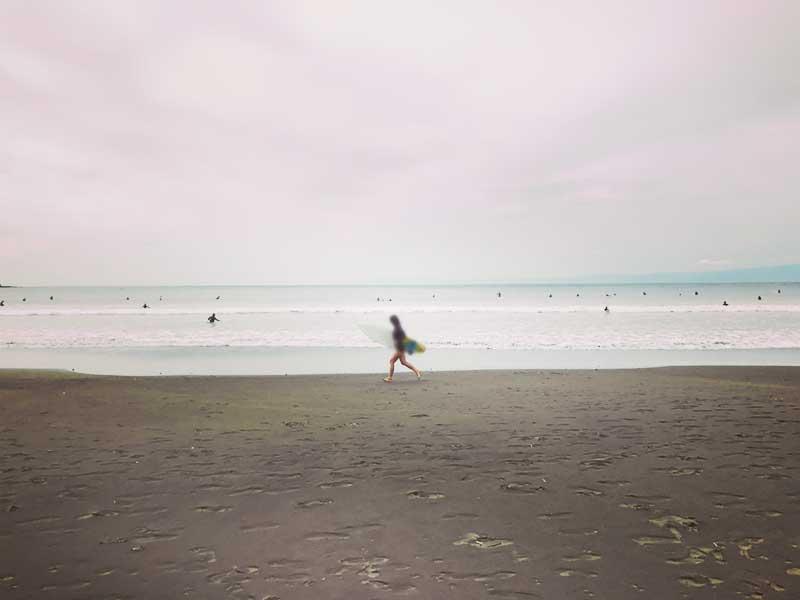 小躍りして波に向かうサーファーの姿