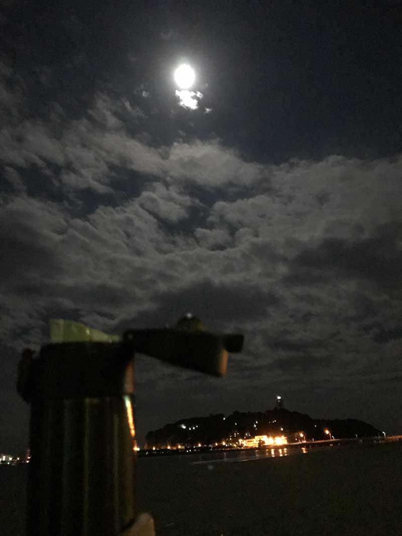 夜の砂浜で月を見ながらホットコーヒー