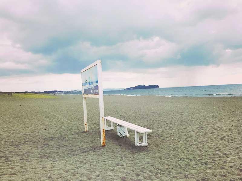 海の方を向いた白いベンチ