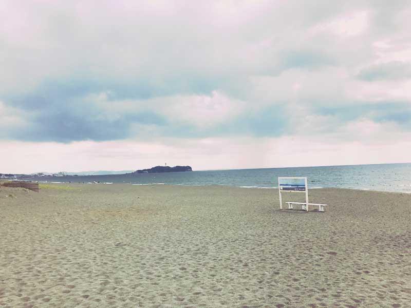 砂浜にポツーンと置いてある白いベンチ