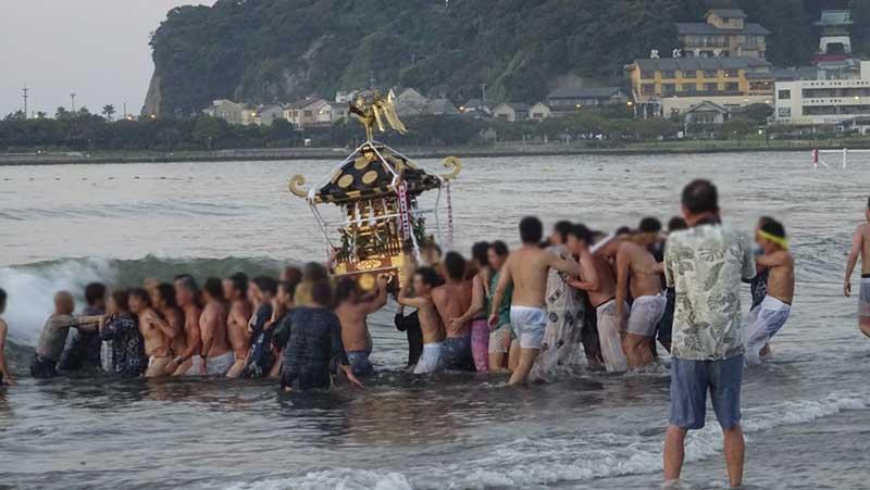 途中何度も波にあおられる神輿と担ぎ手