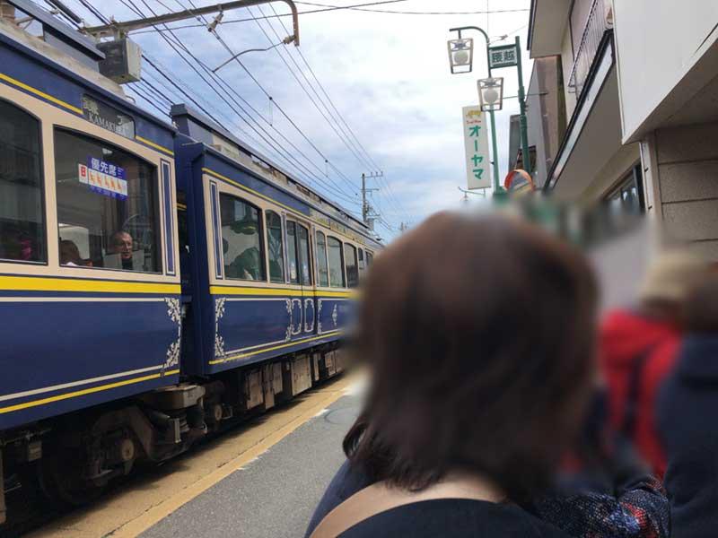 すぐ真後ろを江ノ電が通るスリリングな行列