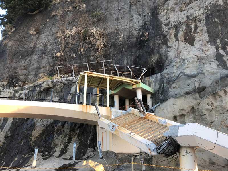 岩屋に渡る橋が捻じ曲がるように瓦解
